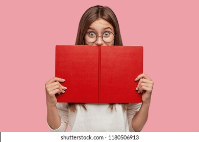 Happy book reader hides behind textbook, has joyful expression, finds out something new, has interesting hobby, wears round big spectacles for good vision. Female geek studies informative topic