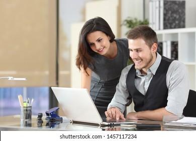 Happy boss teaching intern using a laptop at office