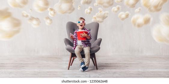 Happy boy in 3d glasses with popcorn in cinema