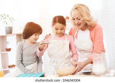 Happy boy with baking dish looks at little girl who whacks dough in bowl with her grandmother. Little grandchildren cook cookies in kitchen with their happy grandmother.