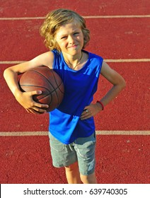 Happy boy with a basketball, outdoor scene