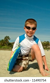 A happy boy at the beach ready for surfing.