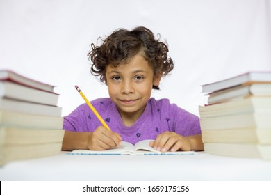 Happy boy between 8 and 10 years old sitting at a desk studying while holding a pencil with textbooks on his table and with a white background