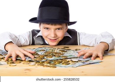 Happy boy in black hat with money on the table, isolated on white
