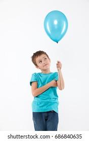 Happy boy with a blue ballon in studio