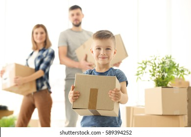 Happy boy with box on blurred background. Moving concept