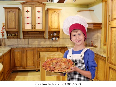 happy boy chef with pizza in kitchen