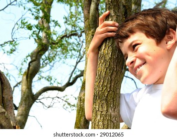 Happy boy climbing in a tree and smiling 'cause the photographer did a funny joke