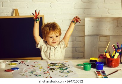 Happy boy colors his hands. Little Children Hands doing Fingerpainting with various colors. Happy kid with paints on hands. Portrait of cute kid having fun, Happy little boy with colored hands