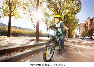 Happy boy cycling on bicycle path in autumn city