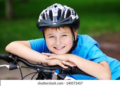 happy boy cyclist holding hands on his bicycle handlebar