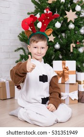 happy boy in deer costume with gift boxes and decorated Christmas tree