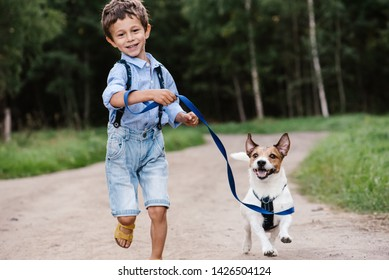 Happy boy with dog on leash running at country road
