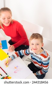Happy  boy drawing picture and his mother looking approvinly on him