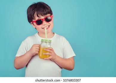 happy boy drinking orange juice on blue background