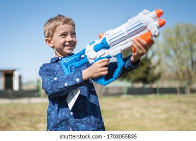 Happy boy with Easter gift - water gun