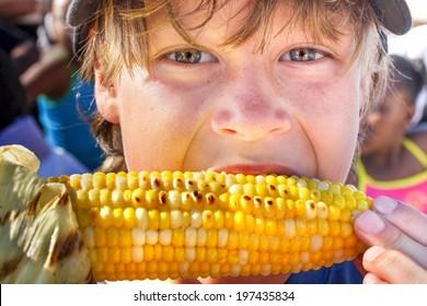Happy boy eating corn on the cob