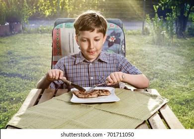 happy boy eating a steak in the garden