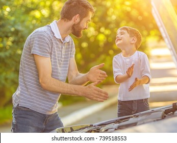 The happy boy and the father fixing a car