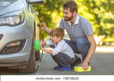 The happy boy and a father washing a car