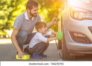 The happy boy and the father washing a car outdoor