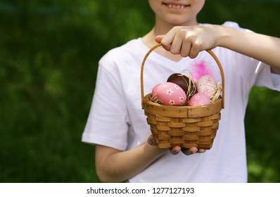 happy boy with festive easter eggs in the park