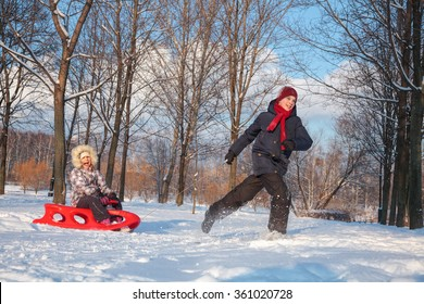 Happy boy and girl  having fun together playing in a snowy winter park. Boy pulling his sister on red plastic sled