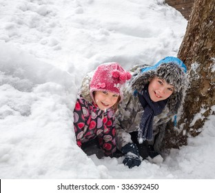 Happy boy and girl looking out from a snow cave they made in a snowdrift