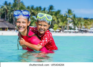 Happy boy and girl playing in the sea. Kids having fun outdoors. Summer vacation and healthy lifestyle concept