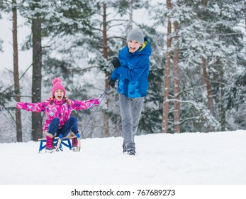 happy boy and girl riding sled and having fun children play outdoors in snow - Christmas Vacation Sled