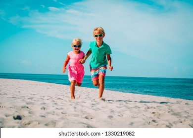 happy boy and girl run at beach, kids play on vacation