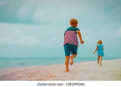 happy boy and girl run on beach