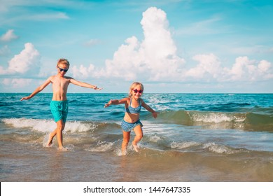 happy boy and girl run play at beach