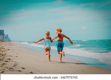 happy boy and girl running on beach