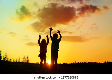 happy boy and girl silhouettes enjoy sunset nature