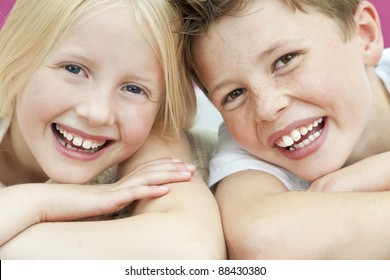Happy boy and girl, sister and brother laughing with big toothy smiles