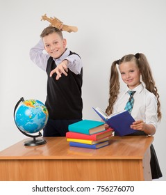 Happy boy and girl sit at a school desk, isolated on white background. Boy plays by airplane. Girl is reading a book. Ideal for banners, registration forms, presentation, landings, presenting concept.