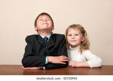 A happy boy and a girl are sitting at the desk in the classroom