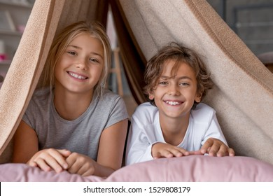 Happy boy and girl sitting in fort from blankets and smiling in camera