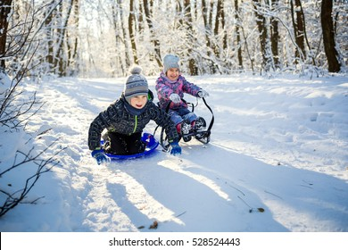 Happy boy and girl sledding from a hill in winter