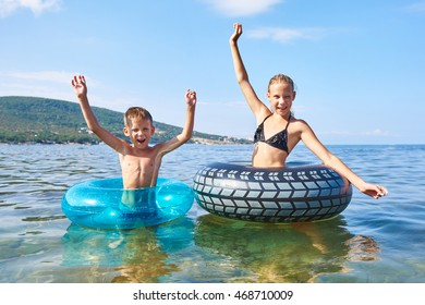 Happy boy and girl swimming with toy lifebuoys