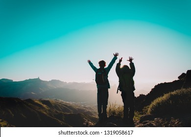 happy boy and girl travel in mountains at sunset, kids enjoy hiking