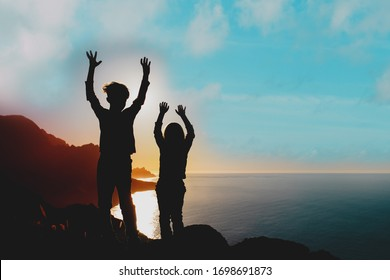 happy boy and girl travel in mountains at sunset