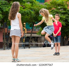 happy boy and girls in elementary school age playing with chinese jumping rope at playground