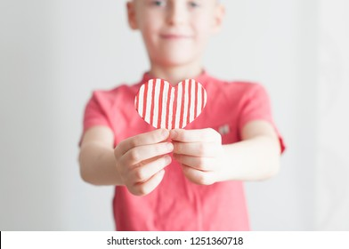 Happy boy giving red stripped heart shape to his mom on white background