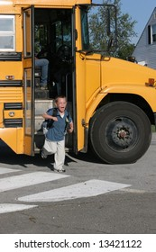 Happy boy with glasses getting off the yellow school bus after the first day of school.