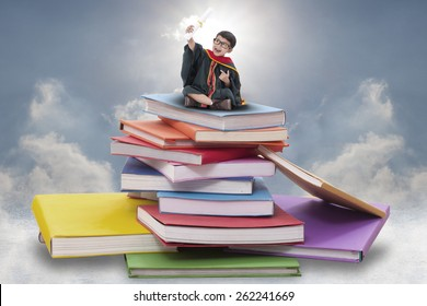 Happy boy in graduation suit sitting on pile of books