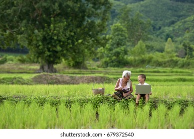 Happy Boy and Grandma use outdoor laptop in Thailand, Asia