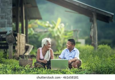 Joyeux garçon et grand-mère utilisant un ordinateur portable à l'extérieur