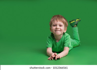 Happy boy in green clothes posing at camera against green background